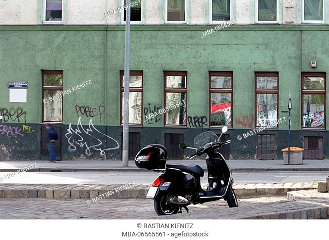 Photography of a scribbled house facade in a hotspot district with parked scooter