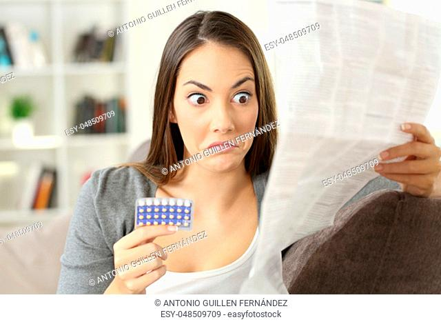 Portrait of a confused girl reading contraindications in a leaflet of contraceptive pills sitting on a couch in a house interior