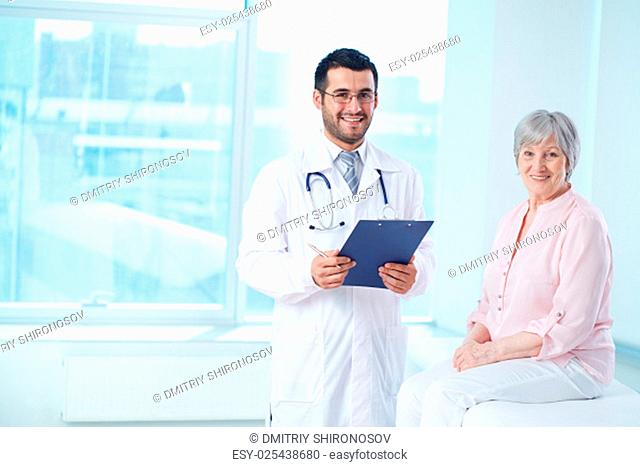 Smiling doctor with clipboard and his patient looking at camera