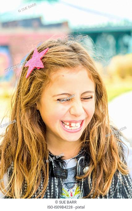 Portrait of girl with long brown wavy hair laughing