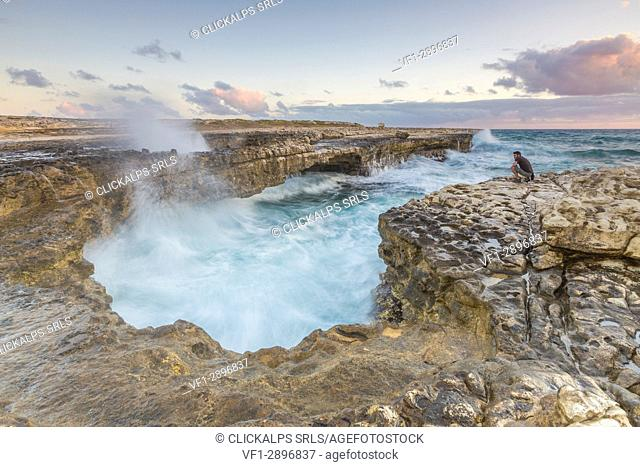 Hiker on the cliffs admires the crashing waves at Devil's Bridge Caribbean Antigua and Barbuda Leeward Islands West Indies
