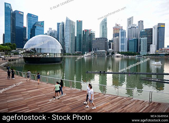 Singapore, Republic of Singapore, Asia - View of the new Apple Flagship Store along the waterfront at Marina Bay Sands with the city skyline of the central...