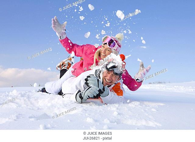 Couple laying together and throwing snow