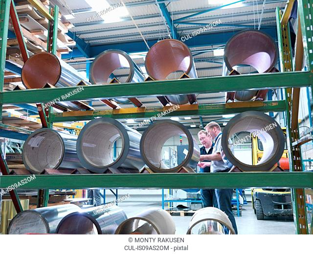Manager and engineer viewed through rolls of laminated metal in engineering factory