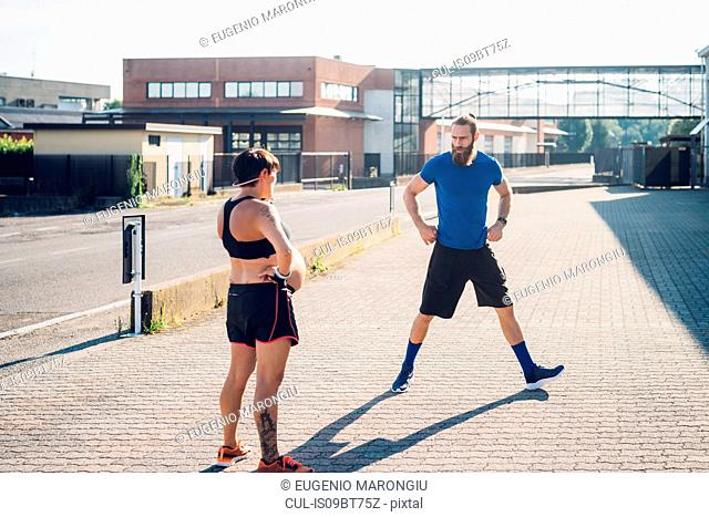 Pregnant woman and personal trainer working out outdoors