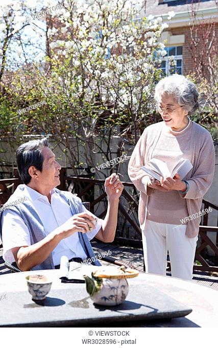 The old couple read in the courtyard