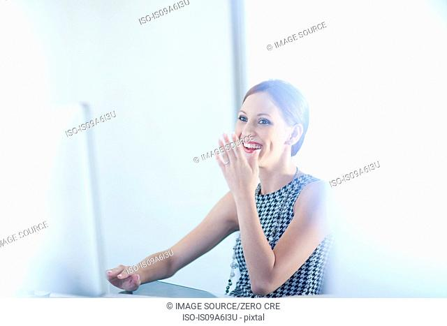 Businesswoman laughing at desk