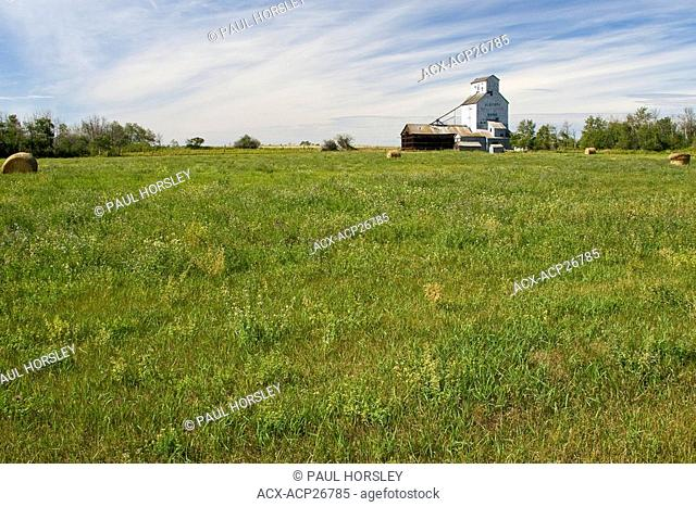 Abandoned grain elevator and summer field, rural Alberta