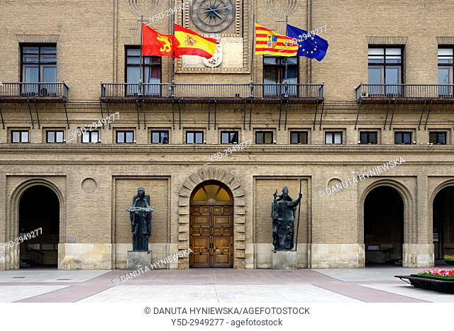 Town hall entrance with statues of Angel of the City and San Valero, 1965, by Pablo Serrano, flags from left to right - Zaragoza, Spain, Aragon, EU