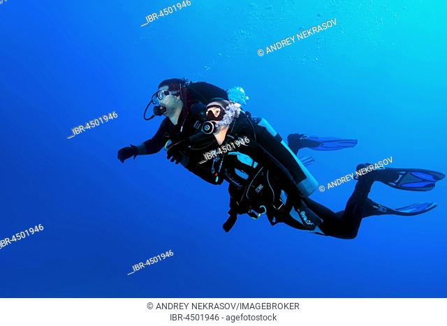 Two scuba divers, man and woman, swimming in blue water, Red Sea, Egypt