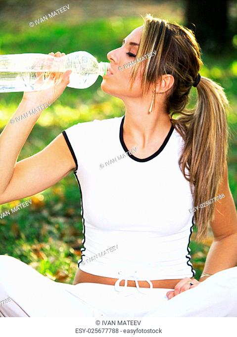 Young woman drinking water outdoors in sports clothing