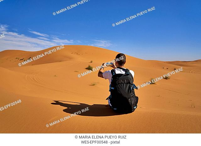 Morocco, man with backpack sitting on desert dune taking picture with smartphone