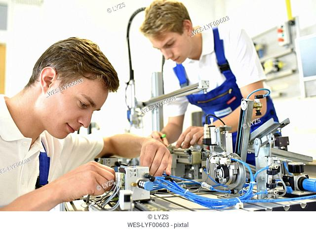 Two students working with pneumatics component parts