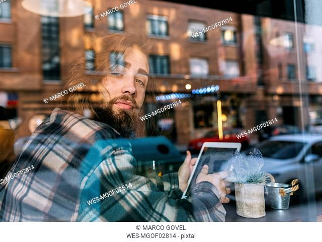 Portrait of stylish young man behind windowpane with tablet in a cafe