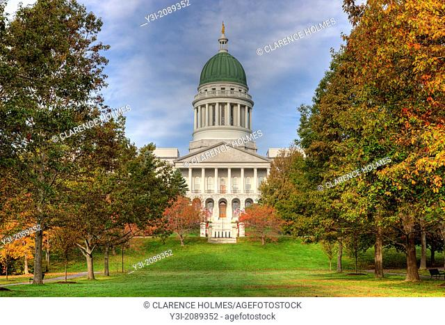 The Maine State House in Augusta, Maine accented by the changing leaves of fall foliage