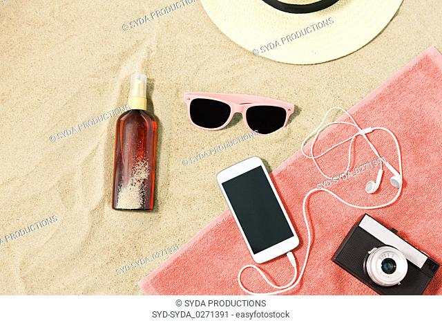 smartphone, camera, towel, hat and shades on beach