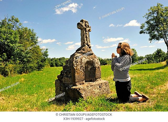 little girl in meditation in front of a stone cross, Cantal department, Auvergne region, France, Europe