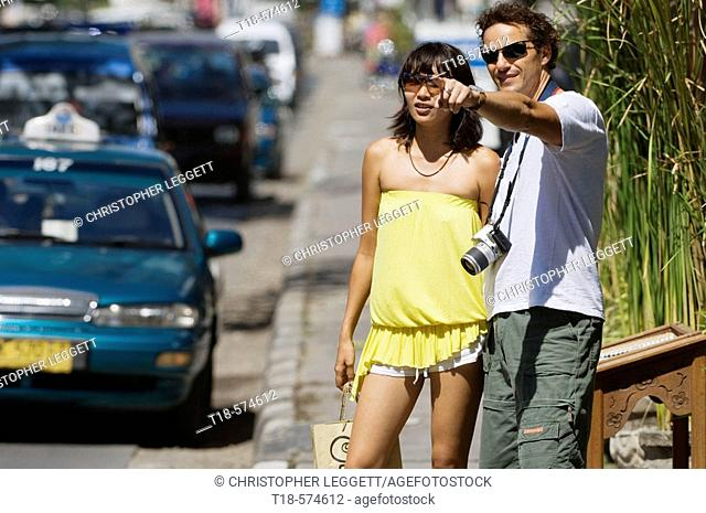 couple standing on sidewalk and pointing