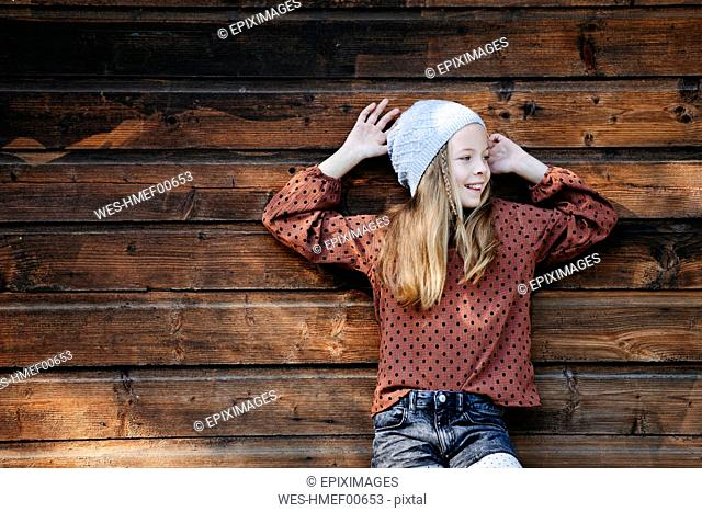 Smiling girl standing in front of a wooden wall outdoors