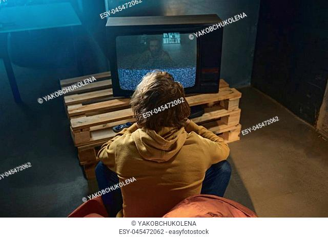 Top view man playing in video game while turning back to camera. He sitting on armchair. Entertainment concept