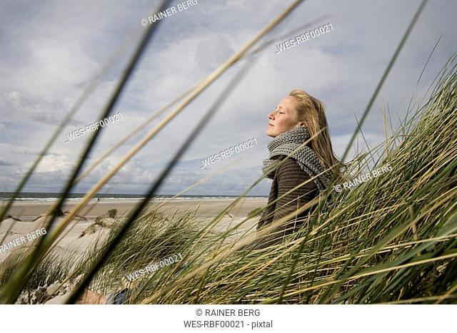 Germany, Schleswig Holstein, Amrum, Young woman on grassy sand dune, eyes closed