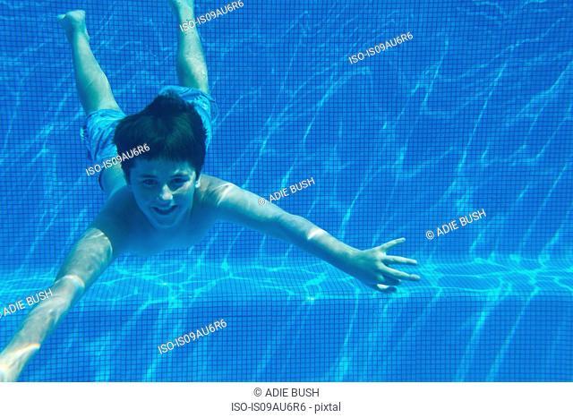 Underwater view of boy underwater swimming in swimming pool