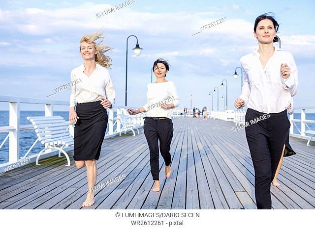 Group of businesswomen running along jetty