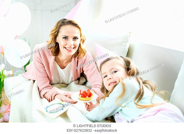 Happy mother and daughter holding tasty strawberry cake and smiling at camera