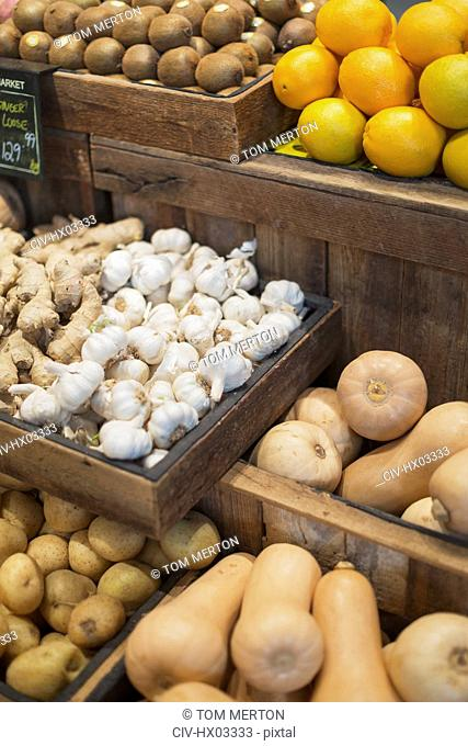 Garlic, ginger, potatoes and butternut squash display in grocery store market
