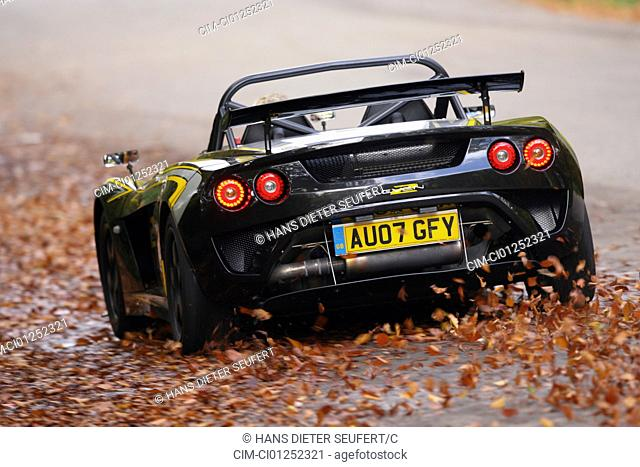 Lotus 2-Eleven, model year 2007-, black-yellow, driving, moving, diagonal from the back, rear view, country road, Herbst, Foliage