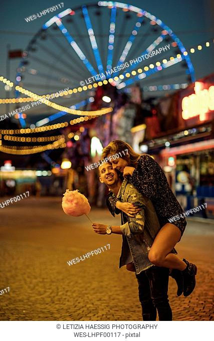 Young couple having fun at a funfair, eating candyfloss