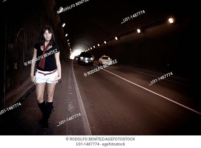 Latin woman in shorts walking along a tunnel