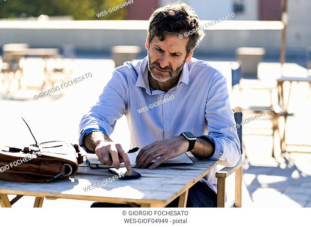 Mature man sitting at outdoor table with cell phone and notebook