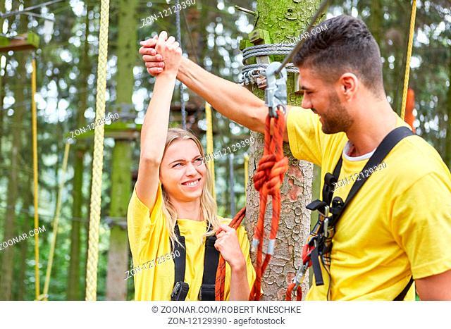 Junges Paar gratuliert sich beim Klettern in einem Kletterkurs im Hochseilgarten