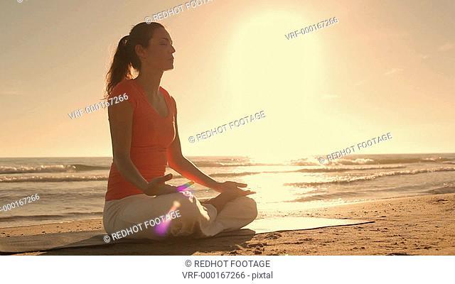 Dolly shot of woman meditating on beach, Marbella region, Spain