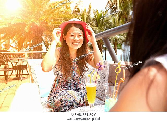 Mid adult woman and daughter having soft drinks at beach cafe, Zhuhai, Guangdong, China