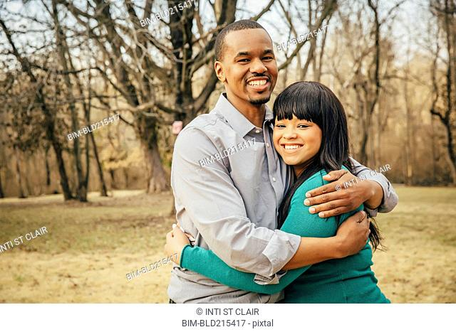 Black father and daughter hugging outdoors