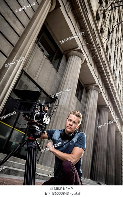 Serious camera operator looking away