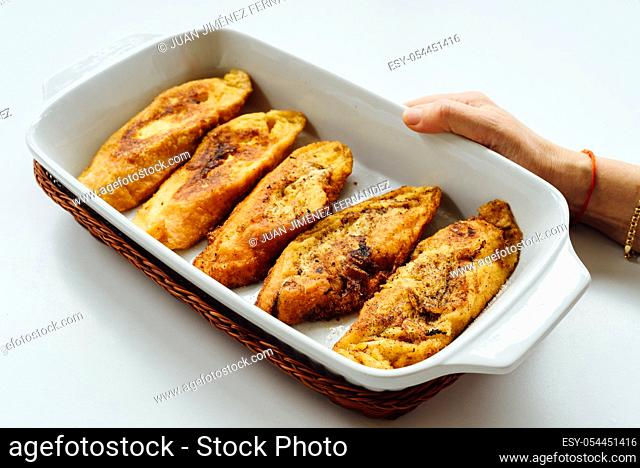 Female hand holding a tray with torrijas, a typical Spanish sweet fried toasts of sliced bread soaked in eggs and milk, on white background