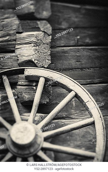 Old wagon wheel outside rural building wall. Rustic wooden nostalgia object