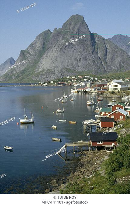 NORWEGIAN FJORD, TRADITIONAL FISHING VILLAGE NESTLED AMID GRANITE PEAKS, REINE, LOFOTEN ISLAND, NORWAY