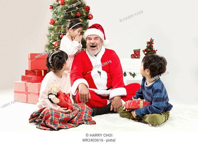 Girl and smiling Santa Claus talking in a whisper, boy and girl looking at them at Christmas