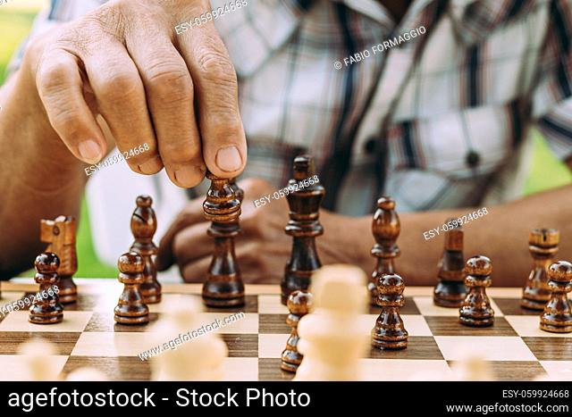 Group of senior friends playing chess game at the park. Lifestyle concepts about seniority and third age
