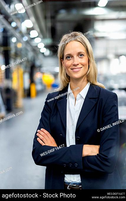 Female manger standing with arms crossed at industry