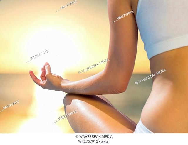 Woman Meditating by sunset