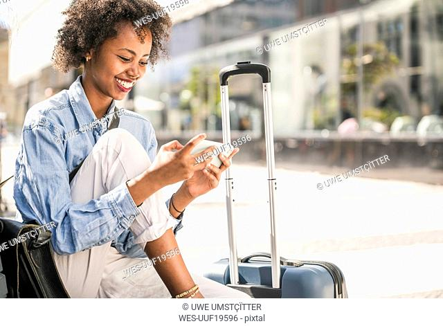 Happy young woman sitting on a bench with suitcase using cell phone