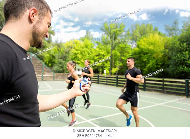Fitness instructor with stopwatch, cardio training outdoors
