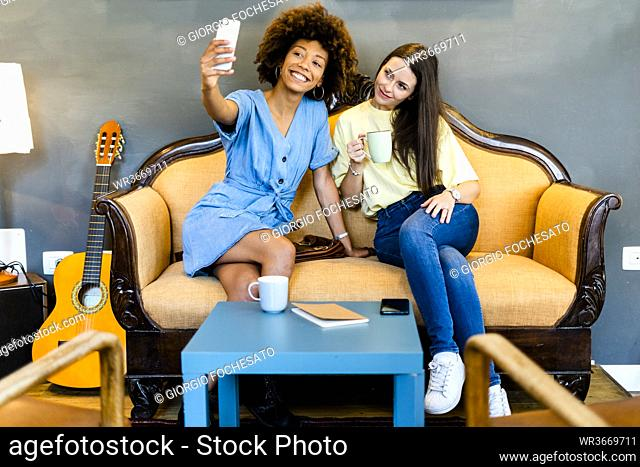 Female friends taking selfie through smart phone while sitting on sofa in modern cafe