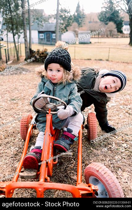 A little girl riding a pedal car with her brother