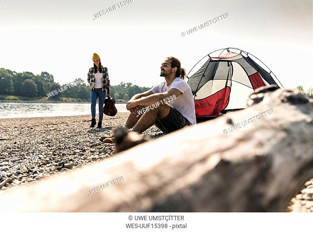 Young couple relaxing at the riverside with guitar and tent